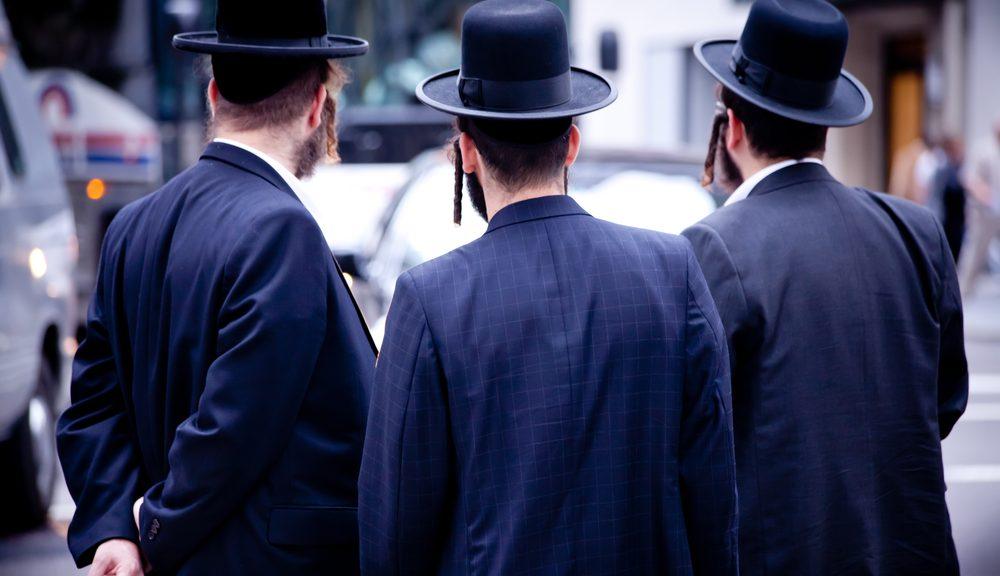 שלושה גברים יהודים עם כובע בעיר מודרנית, עם מכוניות ותנועה על הרקע