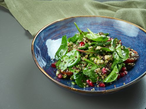 Green salad (spinach) with quinoa and pomegranate seeds in a blue plate on a wooden background. Close up, copy space. vegetarian.